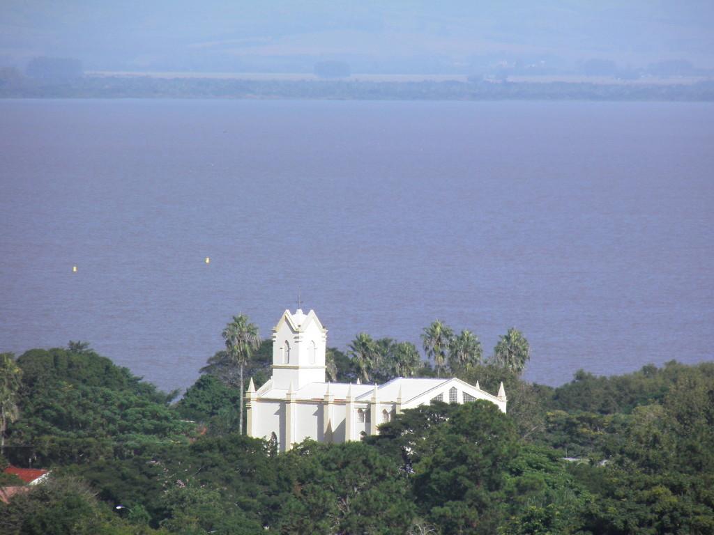 Igreja N. Sra. de Belém Novo e o Guaíba com a Barra do Ribeiro ao fundo