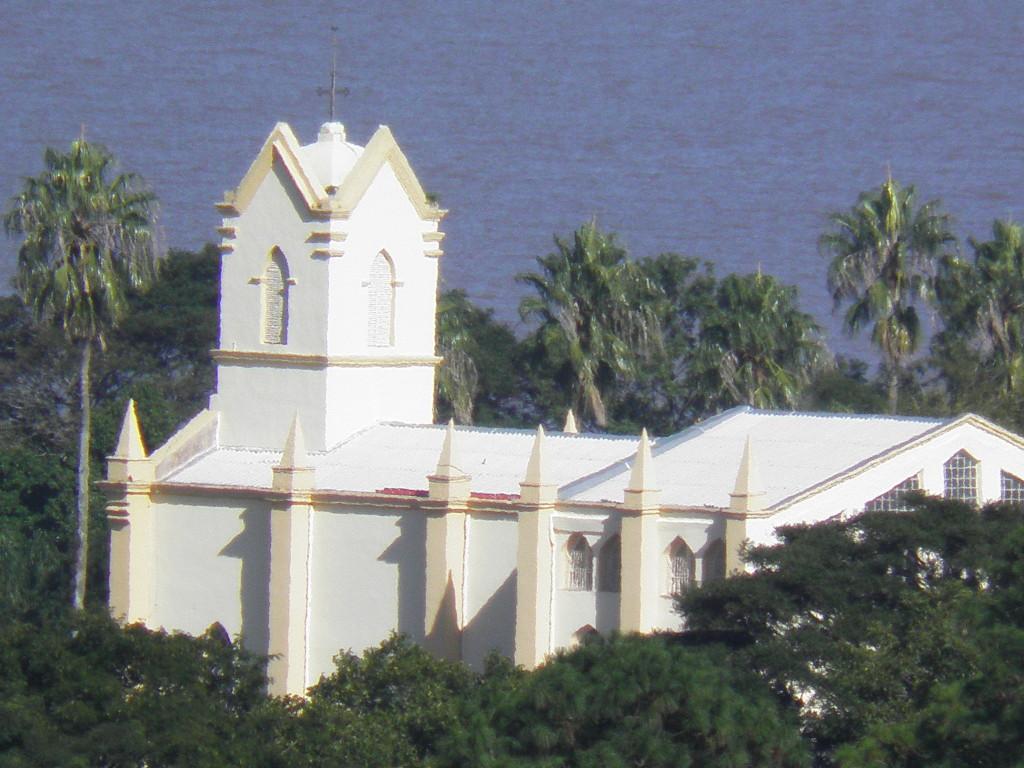 Igreja N. Sra. de Belém Novo entre o verde das copas das árvores.