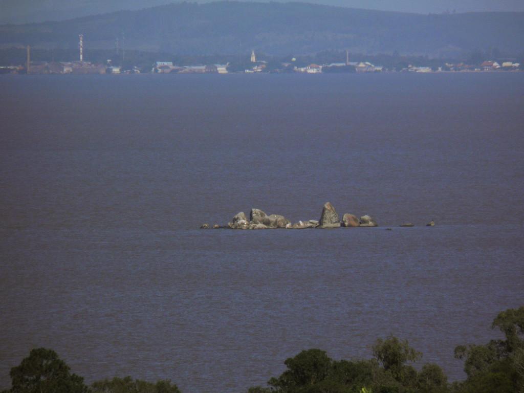Ilha de pedras com a Barra do Ribeiro ao fundo (aparecendo inclusive a torre da igreja matriz de lá)